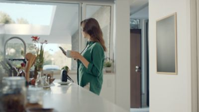 A woman at a kitchen counter, mug in one hand, smartphone in the other, a Hyundai parked in her driveway.