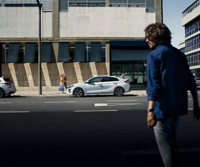A man about to cross the road to get to his parked Hyundai IONIQ. He holds a smartphone in his hand.