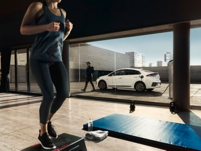 Woman jogging on a treadmill, a Hyundai IONIQ charging in the background