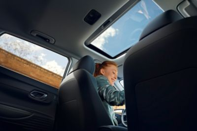 View through the all-new Hyundai i20's open sunroof from the back seat
