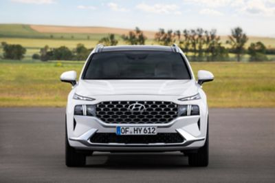 The new Hyundai Santa Fe SUV pictured from the front, parked on a country road