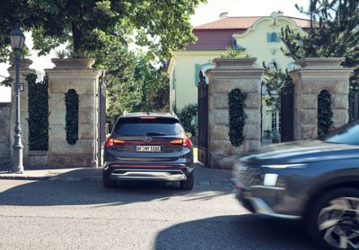 The new Hyundai Santa Fe Plug-in Hybrid 7 seat SUV driving through an entrance gate of a house.