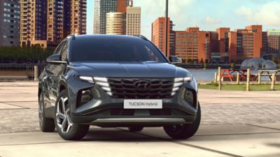 The all-new Hyundai Tucson compact SUV pictured from the front parked near a waterfront skyline.