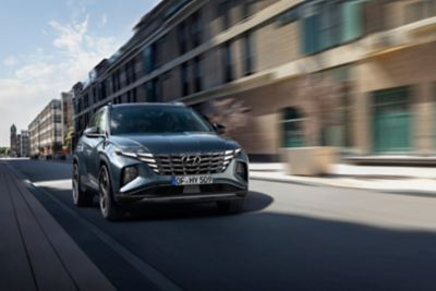 The all-new Hyundai Tucson compact SUV pictured from the front driving down a city street.